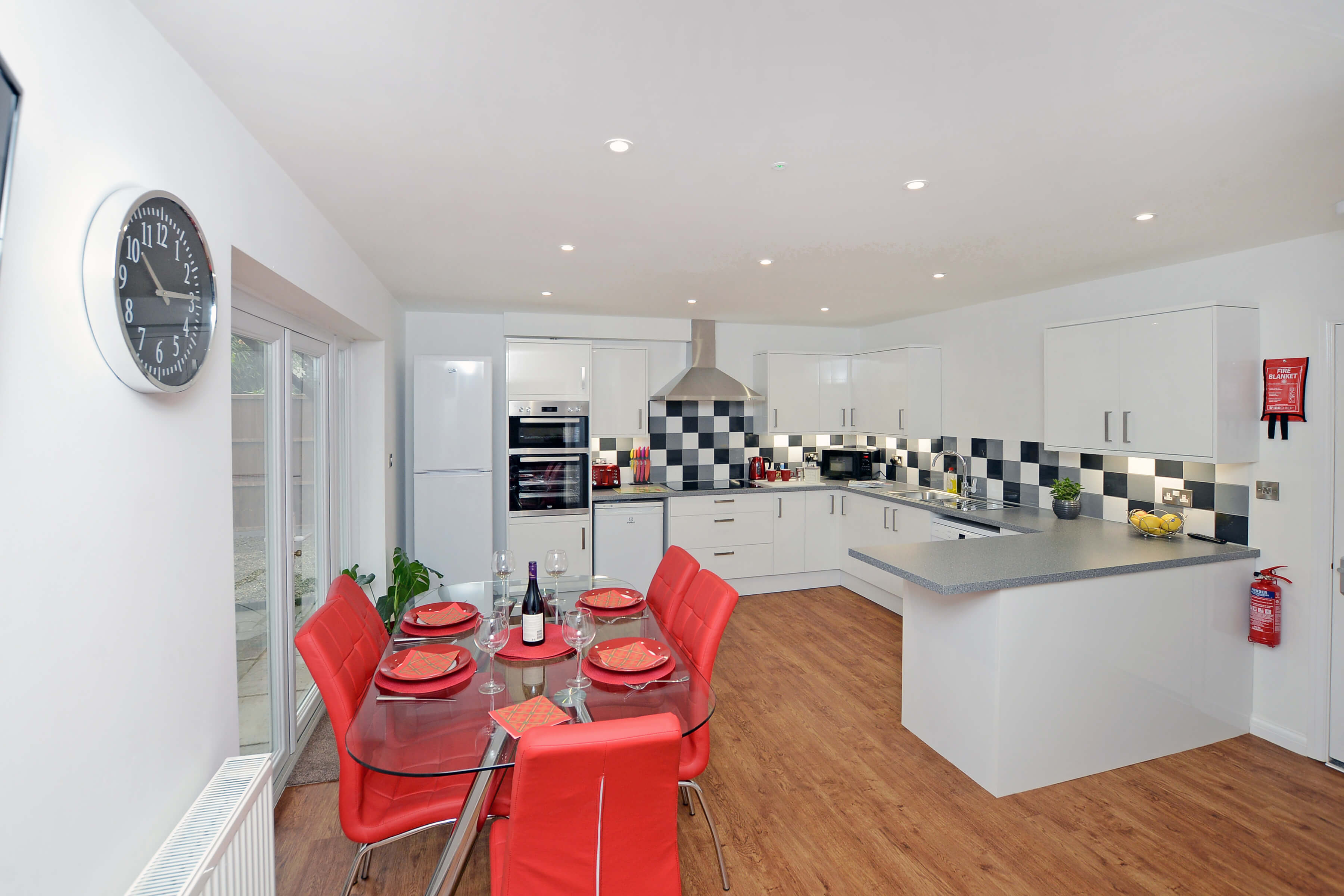 Modern, clean kitchen with white storage units and red chairs. Bottle of red wine on table.