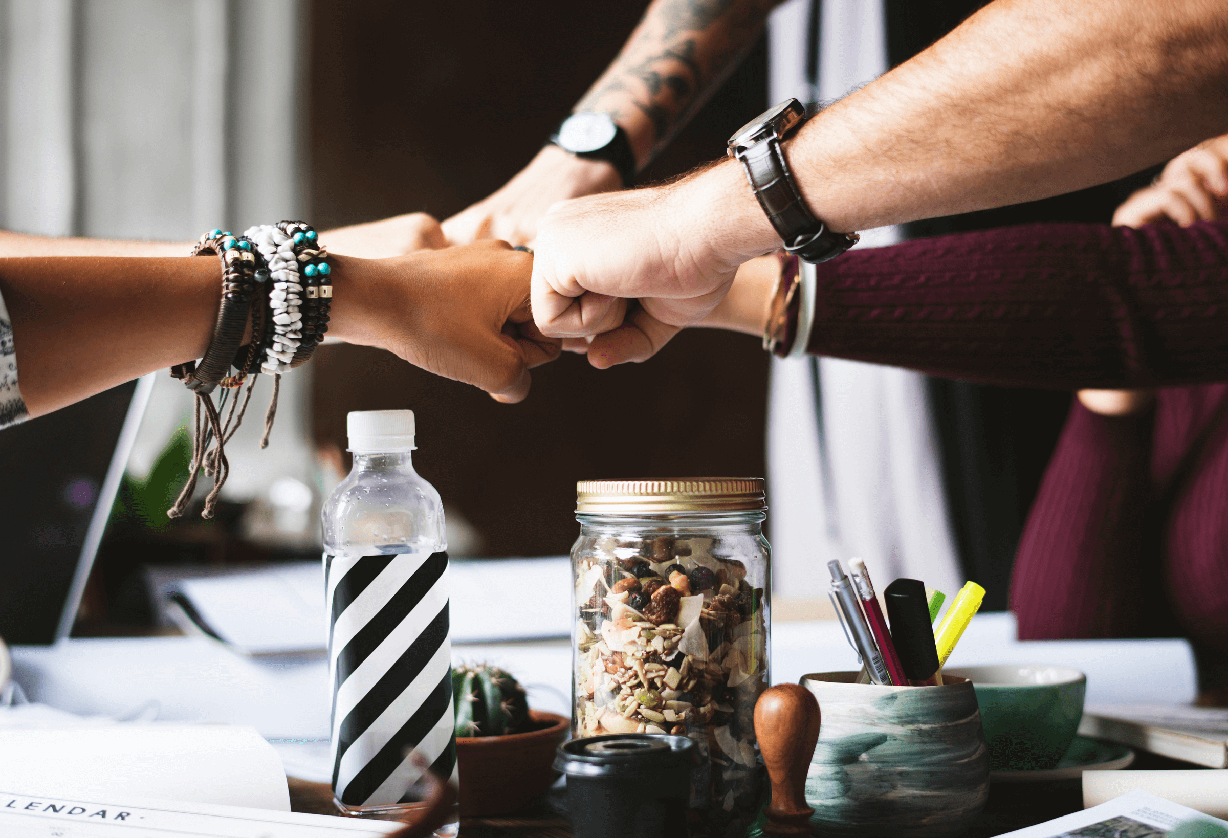 five men and women fist bump over table with paper on - collaborating on ideas